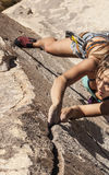 Rock climber clinging to a cliff. Stock Photos