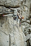 Rock climber clinging to a steep cliff. Stock Photos
