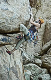 Rock climber clinging to a steep cliff. Royalty Free Stock Photo