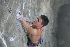 Rock climber clings to an overhang in rock Stock Photo