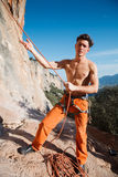 Rock climber collecting belay rope over the mountains Royalty Free Stock Photography