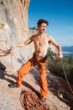 Rock climber collecting belay rope over the mountains Stock Image
