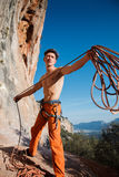 Rock climber collecting belay rope over the mountains Royalty Free Stock Image