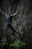 Rock climber dangles in midair as he struggles to climb a challenging cliff. Royalty Free Stock Image