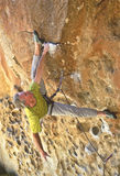 Rock climber dangling from a grip. Royalty Free Stock Photography