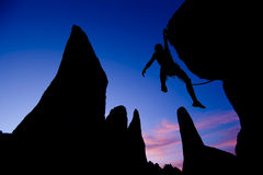 Rock climber dangling by one arm. Royalty Free Stock Photo