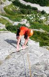 Rock climber dressed in bright colors on a steep granite climbing route in the Alps. A rock climber dressed in bright colors on a steep granite climbing route in Stock Photography