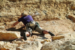 Rock climber girl with the rope. Rock climber on the route with a rope. Rock climbing wall. Wind-eroded rock formations. Picturesque area for climbing Stock Photography
