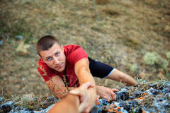The rock climber gives hand for help to the partner Stock Photo