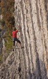 Rock climber on 6-grade climbing route of vertical stone wall Stock Photos