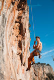 Rock climber hanging on belay rope over the mountains Stock Images