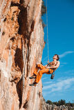 Rock climber hanging on belay rope over the mountains Stock Photo