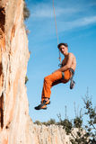 Rock climber hanging on belay rope over the mountains Stock Photos