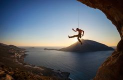 Rock climber hanging on rope while lead climbing Stock Photography