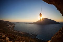 Rock climber hanging on rope while lead climbing Stock Images