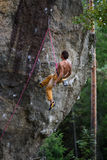 Rock climber having a rest while climbing, with harness and rope. Man abseiling from a steep rock. Outdoor royalty free stock images