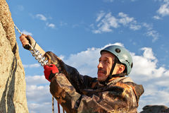The rock-climber in helmet moves on top Stock Photography