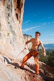 Rock climber holding belay rope over the mountains Royalty Free Stock Photography