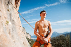 Rock climber holding belay rope over the mountains Royalty Free Stock Photos
