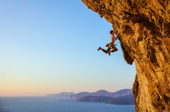 Rock climber jumping on handholds while climbing cliff Royalty Free Stock Photo