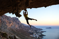 Rock climber jumping on handholds while climbing cliff Stock Photography