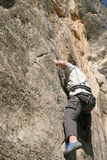 Rock climber. Man climbing on vertical rock being secured Stock Photography