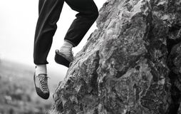 Rock Climber with One Foot Hanging Off Edge of Cliff Outcrop Over Looking Valley Below Stock Images