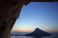 Rock climber on overhanging cliff at sunset Stock Photos