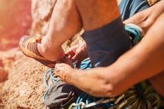 Rock climber put up climbing shoes Stock Image