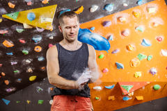 Rock climber putting chalk on hands. In indoor climbing gym Stock Image