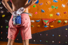 Rock climber putting chalk on hands to prepare for bouldering. Rock climber putting chalk on hands in indoor climbing gym Royalty Free Stock Photos