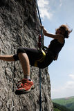 Rock climber rapelling. Young girl hanging on the rocks Stock Photo