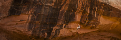 Rock climber rapelling down orange cliff Royalty Free Stock Images