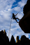 Rock climber rappelling. Stock Photo