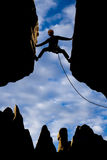 Rock climber reaching across a gap. Stock Photography