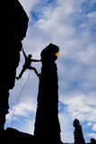Rock climber reaching across a gap. Stock Images