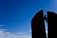 Rock climber reaching the summit. Stock Photos
