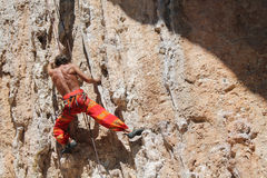 Rock climber in red pants. On the cliff route with a rope. Rock climbing, man musculs Stock Photography