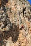 Rock climber in red pants. On the cliff route with a rope. Rock climbing, man musculs Royalty Free Stock Photo
