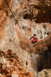 Rock climber in red pants. On the cliff route with a rope. Rock climbing, man musculs Stock Image