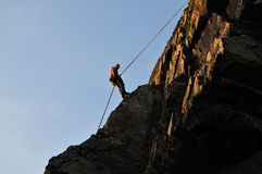 Rock climber repelling Stock Photo