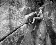 Rock climber on rock face. Black and white photograph of rock climber on sheer rock face Royalty Free Stock Photos