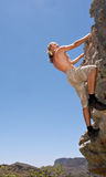 Rock climber on rock scrambles up Stock Photo