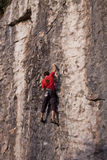 Rock climber rope dangling on vertical difficult stone wall Royalty Free Stock Photography