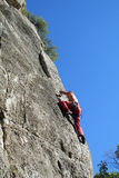 Rock climber with the rope. Rock climber on the route with a rope. Rock climbing wall. Wind-eroded rock formations. Picturesque area for climbing Stock Images