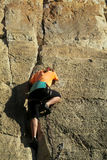 Rock climber with the rope. Rock climber on the route with a rope. Rock climbing wall. Wind-eroded rock formations. Picturesque area for climbing Stock Photos