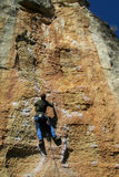Rock climber on the rope. Rock climber on the route with a rope. Rock climbing wall. Wind-eroded rock formations of red and yellow stone. Picturesque area for Royalty Free Stock Images