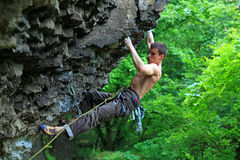 Rock climber on route. With bright green foliage in the background Stock Photography
