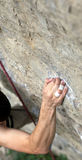 Rock climber's hand grasping handhold on cliff Royalty Free Stock Photography