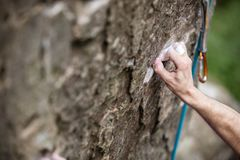 Rock climber`s hand gripping small hold on natural cliff Royalty Free Stock Photo